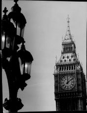 A dramatic black and white photograph on the bell tower Big Ben's dial with an old-fashioned street lamp in the foreground.