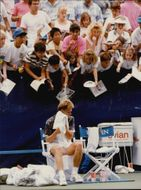 Stefan Edberg wipes himself with a towel while a bunch of fans ask for autographs from the stands during the US Open 1996