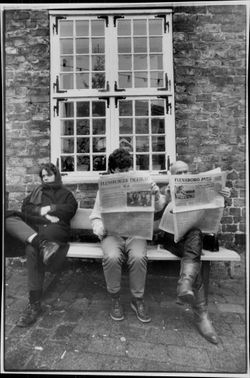 A Danish newspaper and a German newspaper are read side by side on a park bench