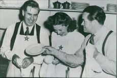 Henry A. Wallace, Vice President of U.S. visit  Canteen for servicemen, in apron and washes dishes during visit to the Hollywood Canteen assisted by Bob Hope, radio and film comedian and Dinah shore, radio singer. 1944