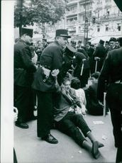People during a rally with policemen on guard in Paris.  Taken - June 1960