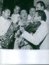 A group of musicians having fun with Columnist Elsa Maxwell.