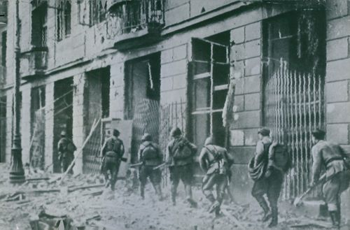 Russian machine gunners advance through the rubble of the streets of Praga, industrial suburd of Warsaw.