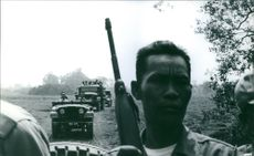 Close up of a soldier in military vehicle, passing by the field.