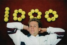 """Tennis player Stefan Edberg poses at the text """"1000"""" written with tennis balls after his 1000th match played during the Eurocard Cup 1995"""