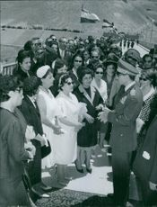 A military officer welcoming the women, people are watching around them, June 1963.