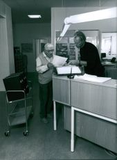 A photo of a old man holding a paper , reading and asking something to the man  whose in charge in information table beside them is a cart carrying books.