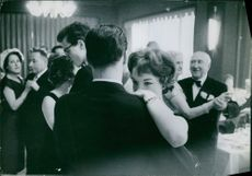 Couples dancing in a party. 1959.