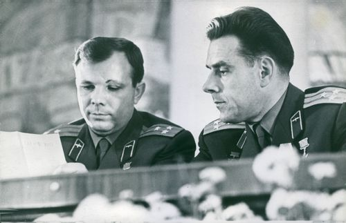 Two military officers seated next to each other and reading a note.