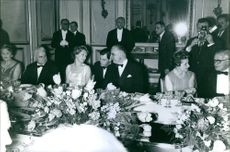 Former British Prime Minister Harold Wilson is sitting with his wife Mary Wilson in a dinner party, while Mary is discussing something with former French Prime Minister Georges Pompidou