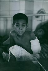 A wounded child looking towards camera.