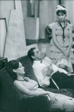 Catherine Millinaire sitting with a man on sofa. Photo taken July 31, 1961