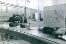 Policemen talking to a lawyer in the room.