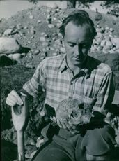 An archeologist holding and looking at skull.