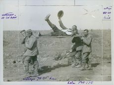 An injured soldier being lifted by other soldiers, waving and smiling. 1916