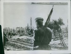 Soldier guarding in street and looking at the other people passing by.  The war Eastern Campaign The Austrian town Sinyava, taken by the Russians.