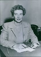 Frances G. Knight sitting at her desk in her office.