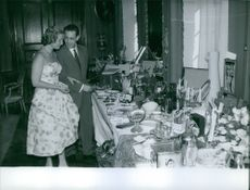 Man and woman looking at silverware on the table.