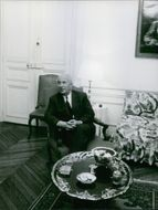 1969  A photo of a French Socialist politician Gaston Defferre sitting alone, looking towards something and smiling in a room.