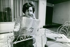 Lucía Hiriart reading a newspaper.