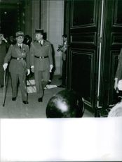 Maurice Challe walking with a old men, while both of them in military uniform.1961