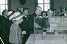 People looking at a crown on a glass display case.