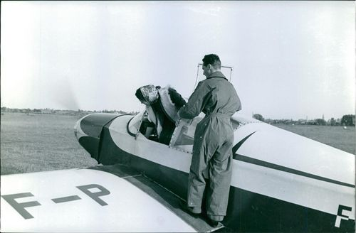 Xavier, Duke of Parma and Piacenza assisting a woman to come out from airplane cockpit.