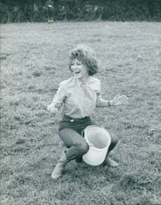 Irina Demich balancing herself while holding bucket in between her legs.