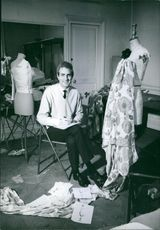 Man sitting in his dress workshop and looking towards camera.  1962