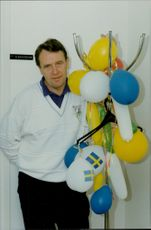 Football coach Nisse Andersson holds balloons.