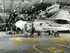 "An A-6 ""Intruder"" aircraft is being reviewed on the hangar deck aboard the USS Independence aircraft carrier"