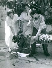 Man and women holding and taking away a wounded man.