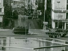 Soldiers sitting in army tank on road.