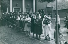 Women behind the rope in a crowd are smiling and clapping their hands, in 1963.