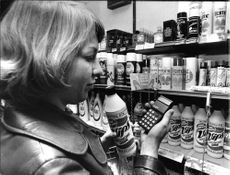 Woman with calculator in supermarket