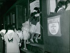 Women and children getting into train.