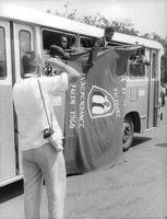 A photographer taking photos of Congo people inside a bus holding a flag for independence. 1960