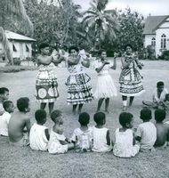 People performing in front of the little children.