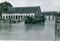 A flooded area with military tank and truck crossing in Vietnam, 1966.