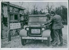 Allied War Supplies Roll From Antwerp to Front.  Edward F. Seymour of Los Angeles, California, commander if an ABC truck convoy and private Douglas Dederor of Fairfield, Connecticut, American soldier serving at a surge pool, sign the necessary papers befo