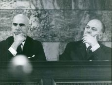 Stylianos Pattakos with another man sitting and looking at something.