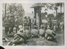 Soldiers gathered in the field while the other soldiers siting during Tyskland war, 1915.