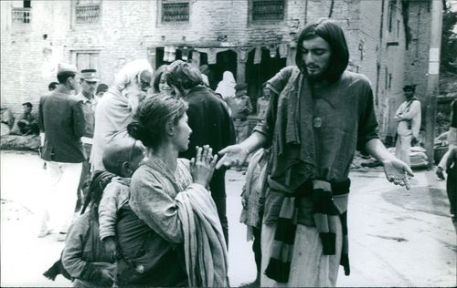 A poor woman talking to a man standing beside her in street.