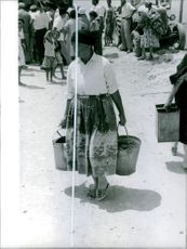 An old woman carrying a buckets in her hands in Cyprus, 1964.