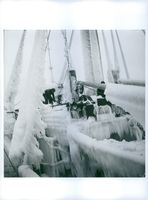 A men removing ice from a frozen ship.