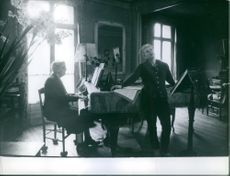 Man playing piano, while Jane Marie Andree Rhodes singing in home.