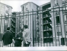 Three men standing together by high fence and building in Paris.