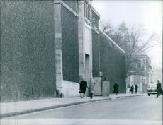 People walking on the sidewalk, beside a building. 1960