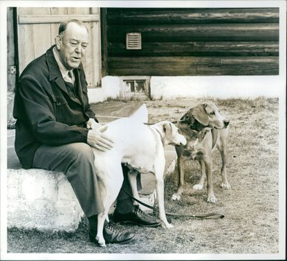 A photo of Norwegian politician Trygve Lie sitting with his two dogs.