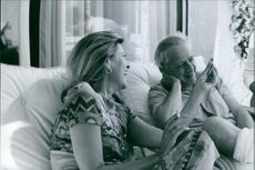 """A photo of a Greek Actress Melina Mercouri sits beside her husband Julius """"Jules"""" Dassi in the couch and is having a conversation."""
